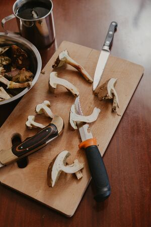 Mushroom still life. Halves of raw mushrooms and three knives lie on a cutting board. Near metal dishes