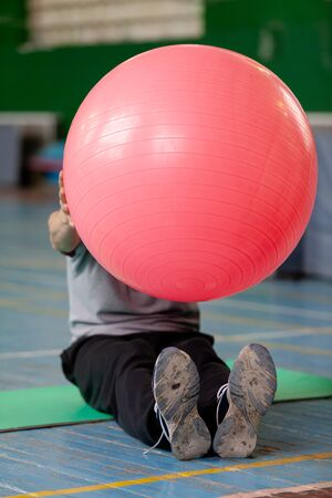 instructor sits on the floor of the gym and holds in front of him a large pink fitball for aerobics 写真素材