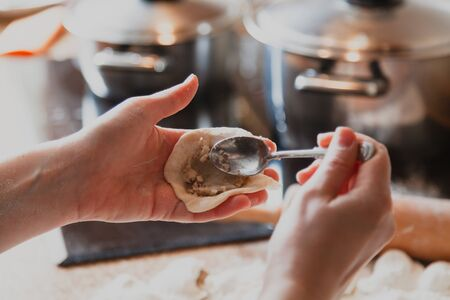 hand puts a stuffing in the dumpling with a teaspoon. In the background metal pans