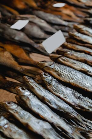 Fish series in the bazaar. A group of dried fish ram lies on the counter in the market