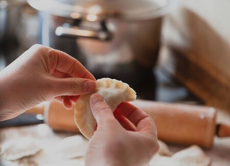 woman's hands are making a damp dumpling. In the background a metal saucepan and a wooden rolling pin