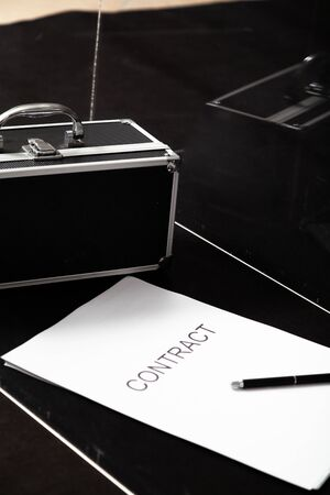 Transparent business. A contract printed on paper and a portable safe for money lies in a glass box. The pen is on top of the contract