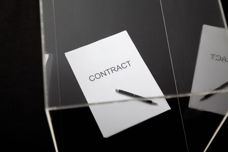 Transparent contract. A contract printed on paper and a pen lies in a glass box close-up