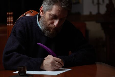 man with a beard sits at a large polished table and writes on a white sheet using a goose feather and inkwell.