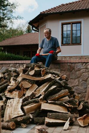 After work. A gray-haired man with a beard in a T-shirt is sitting in the yard on a stone fence. Under it lies a large pile of firewood. 写真素材