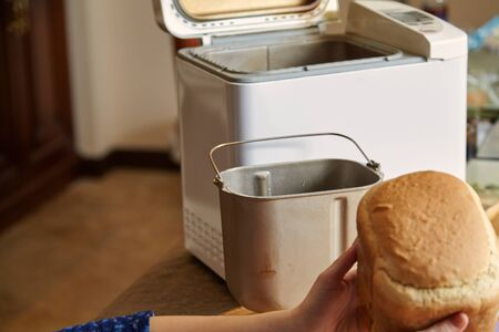 woman hands hold fresh bread from the bread baking mold of the electric bread maker. There is a big knife nearby. Stock Photo