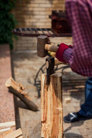 Strong log. Four hands in red gloves chop a round log with an ax and a sledgehammer on a stump in a summer yard