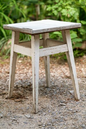 wooden stool with a square seat stands on the ground in the yard