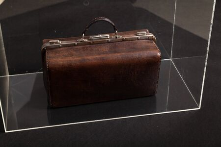 Exhibit in the museum. Antique leather carpetbag standing in a glass box 写真素材