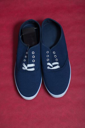 Two new blue sneakers with white soles and laces stand on a red isolated background.
