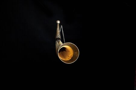 Souvenir horn for alcoholic drinks on a chain on a black background. The edges of the horn inlaid with metal