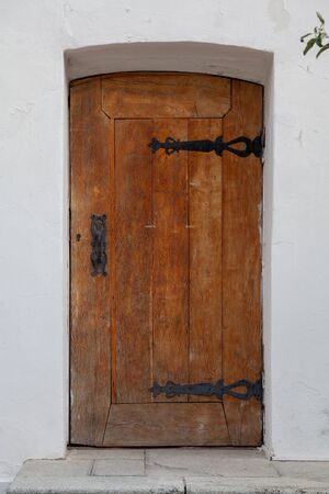 Brown arched wooden antique door on a white stone wall of a medieval church building
