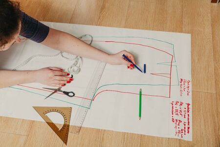Designer creates a model. Female hands with a manicure do the layout of the sewing pattern on paper