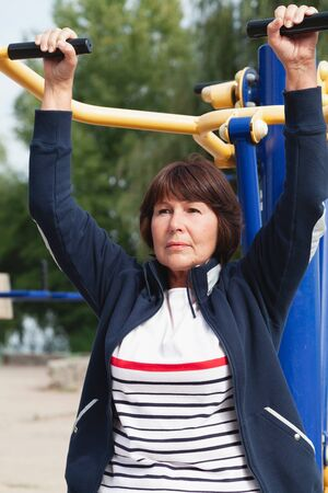 Pretty active elderly woman performs physical exercises on the street exercise machine of the playground Stok Fotoğraf