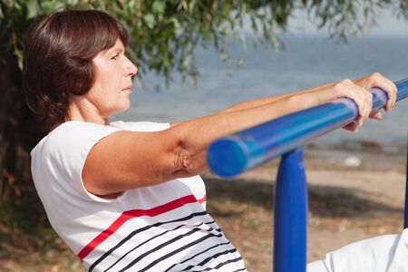 Gymnastics on the river bank. Cute elderly woman performs health exercises on metal bars
