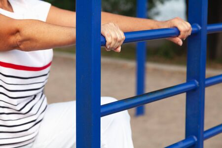 Gymnastics for seniors. Hands of an elderly woman tightly grasped the metal bar of the gymnastic staircase