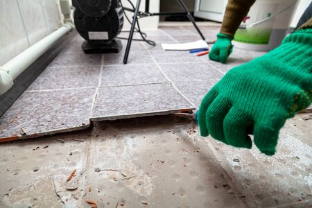 dismantling of tile. Hands in green working gloves undermine the broken tile with a chisel.