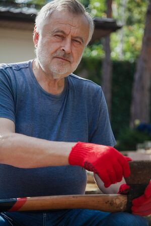 Portrait of an elderly man with an ax. A gray-haired man with a beard in a T-shirt is sitting in the yard. Holding an ax on a long handle