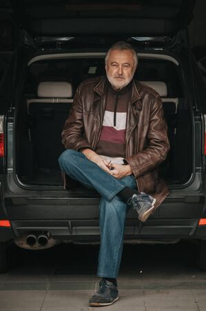 elderly man in a leather jacket sits in the open trunk of a car in a garage