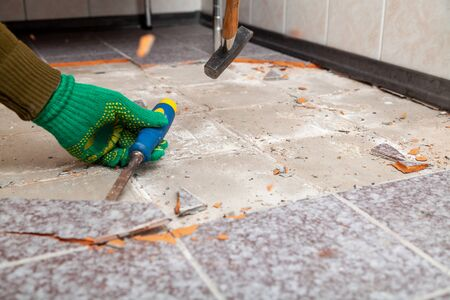 dismantling of tile. Hands in green working gloves undermine the tile with a chisel and a hammer