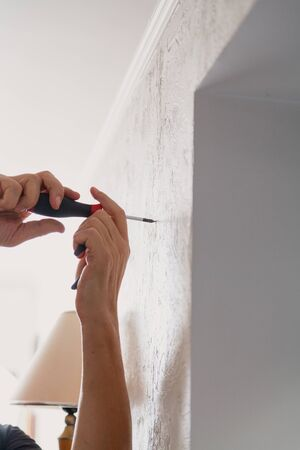 Homework. Hands screw the screw into a vertical wall with a hand tool.
