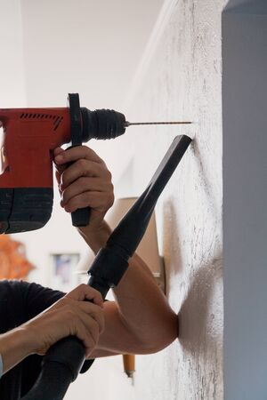 Homework. Hands drill a hole in a vertical wall with a drill. Next hand collects dust with a vacuum cleaner Stok Fotoğraf