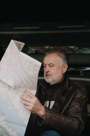 elderly man with a gray beard in a leather jacket folds a road map against the background of an open trunk of a car