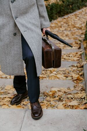 Men's autumn fashion. Man in stylish shoes and a white coat. Stok Fotoğraf