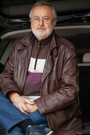 Portrait of a man with a gray beard. An elderly man in glasses and a leather jacket against the background of an open trunk of a car