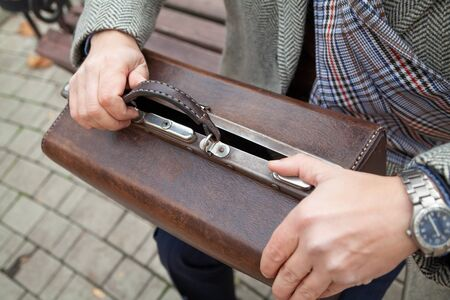 man in a gray coat sits on a wooden bench. Opens a brown leather carpetbag in retro style. Close-up