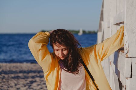 Nice girl in a yellow jacket rests on a white wooden structure on a sandy beach