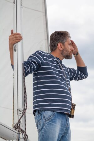 captain holds on to the mast. A man in a striped sweater and jeans sits on the nose of a sailing yacht and looks through binoculars