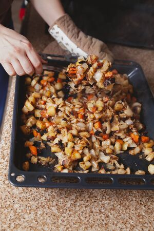 Appetizing vegetable stew. Large steel spoon stirs baked vegetables in a metal baking sheet