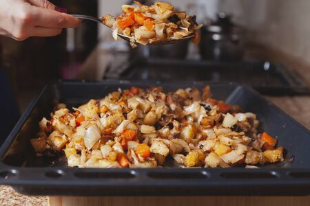 Spoon over a baking sheet. A large steel spoon filled with baked vegetables over a metal baking sheet