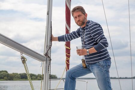 Businessman with a beard in a striped sweater stands on the nose of a white yacht and drinks whiskey from a glass