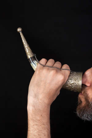 man with a beard holds his horn for wine with his left hand and drinks from it. Profile view Stock Photo