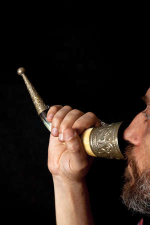 man with a beard holds the horn for wine with his right hand and drinks from it. Profile view Stock Photo