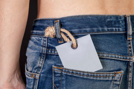 gray cardboard label sticks out in the back pocket of a trendy blue jeans close-up. Top naked body