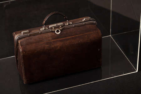 Exhibit in the museum. Antique leather carpetbag standing in a glass box Reklamní fotografie