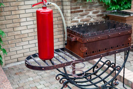 Barbecue and fire extinguisher. A large red fire extinguisher stands on a forged barbecue in the yard Stock Photo