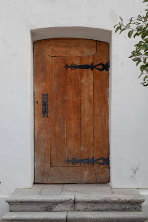 Branch of an apple tree with green leaves reaches for an old church wooden door on a white stone wall
