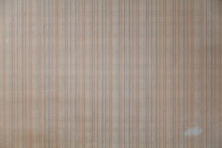 Wall with wallpaper with a small checkered pattern. Vertical thin yellow and green lines. Thin gray lines located horizontally
