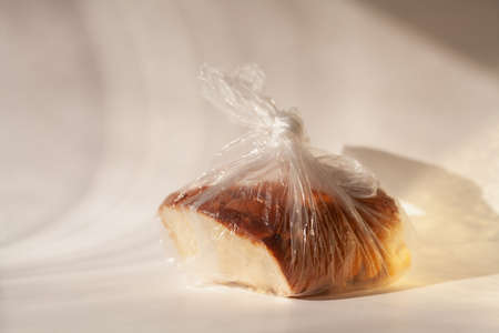 Part of a cut loaf of white flour bread lies in a tied plastic bag on a white background Reklamní fotografie - 155682418