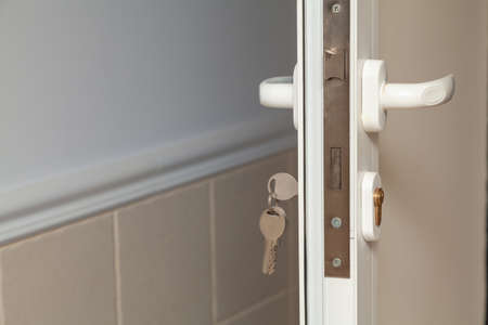 Plastic door profile. Mortise lock with two handles inside a plastic interior door. Keychain inserted on the left