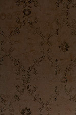 texture of the old wallpaper. Yellow wallpaper with a green pattern in the form of a monogram close-up. The spots are clearly visible