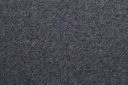 Texture of gray woolen fabric with a rough surface close up
