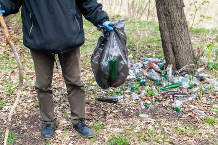 We save nature from garbage. Man with blue rubber gloves collects discarded glass bottles in a black plastic bag in the forest