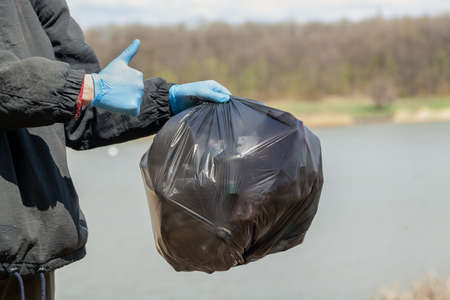right thing to do. The hand of the ecologist in blue rubber gloves holds a black plastic bag with garbage on the shore of the reservoir. Right hand shows sign of approval