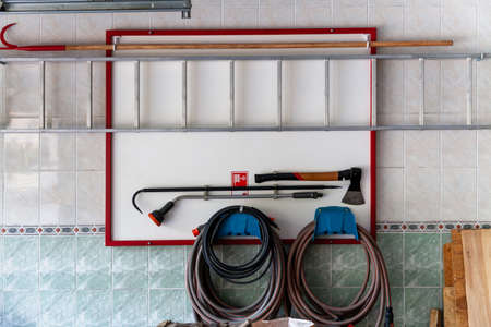 Fire safety place. A white shield weighs on the wall on which hangs an ax, a hook, a hose and an aluminum ladder