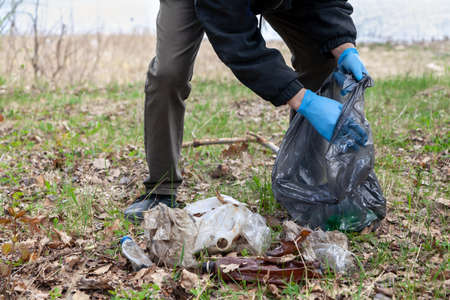 We save nature from garbage. A man in blue rubber gloves collects plastic garbage in a black bag on the shore of a pond Reklamní fotografie - 156564586